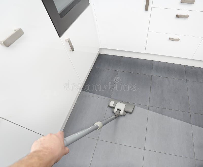 El limpiar con la aspiradora en la cocina sucia fotografía de archivo libre de regalías