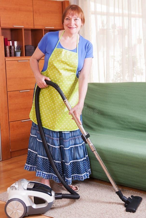 El limpiar con la aspiradora maduro de la mujer foto de archivo libre de regalías