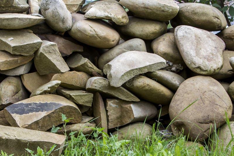 El Lit por la pila del sol de diversos tamaños crackled grandes y las formas encienden piedras marrones suaves en hierba verde Re fotografía de archivo libre de regalías
