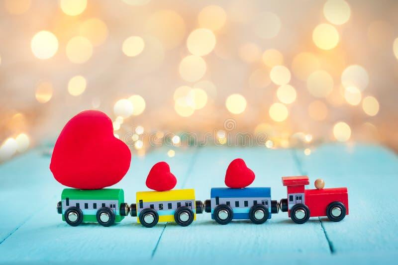 El llevar colorido miniatura del tren los corazones rojos onwooden el fondo de la turquesa con el bokeh del brillo foto de archivo