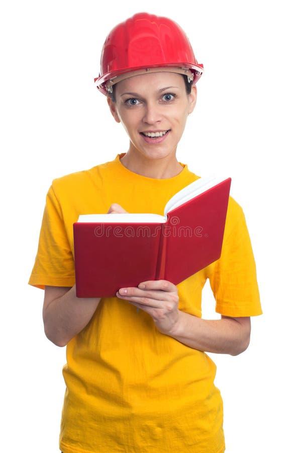 El llevar de la mujer protege el casco y las notas de la fabricación fotografía de archivo libre de regalías