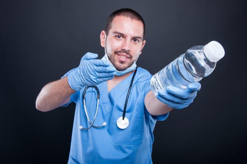 El llevar del médico friega mostrar la botella de agua fotos de archivo libres de regalías