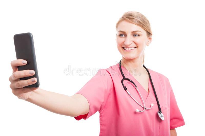 El llevar femenino de la enfermera friega tomar el selfie con smartphone imagen de archivo libre de regalías