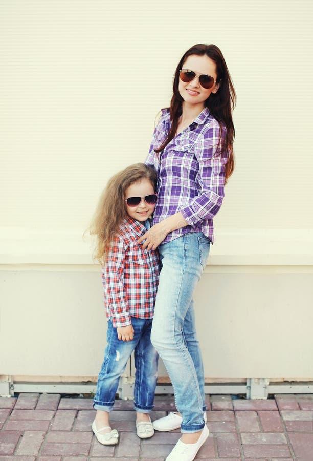 El llevar hermoso de la madre y del niño camisas a cuadros y gafas de sol imagen de archivo