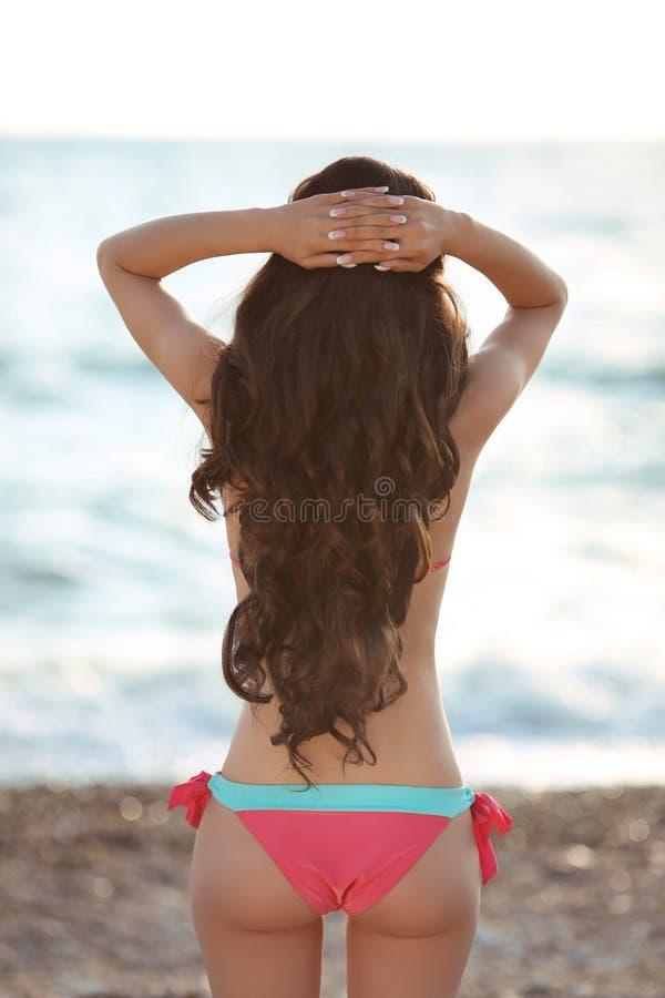 El llevar modelo de la muchacha morena delgada hermosa en el bikini res de la moda imagen de archivo