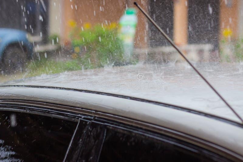 El llover en el tejado del coche fotografía de archivo