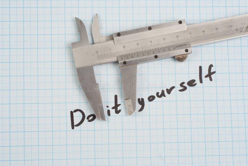 El ` lo hace usted mismo el ` - tornillo, nueces y calibrador en el papel cuadriculado fotografía de archivo libre de regalías