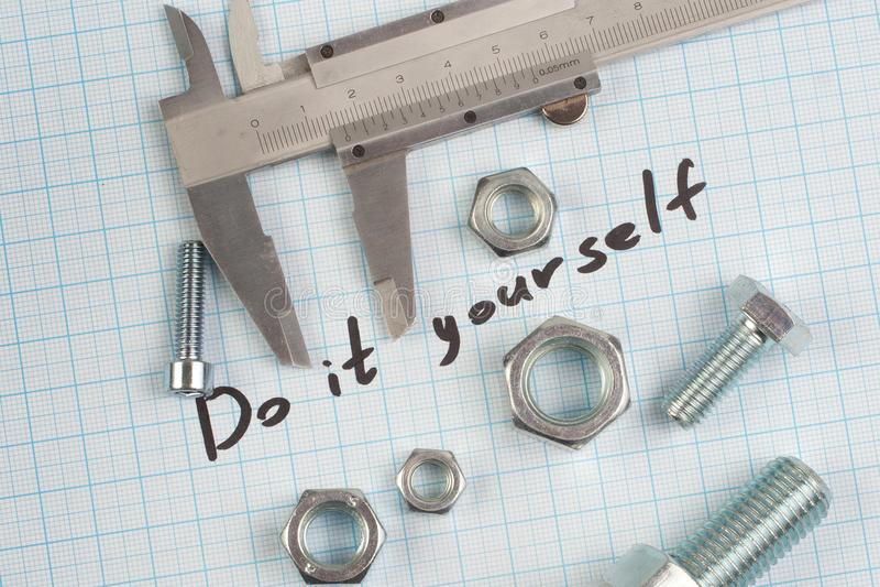 El ` lo hace usted mismo el ` - tornillo, nueces y calibrador en el papel cuadriculado fotografía de archivo