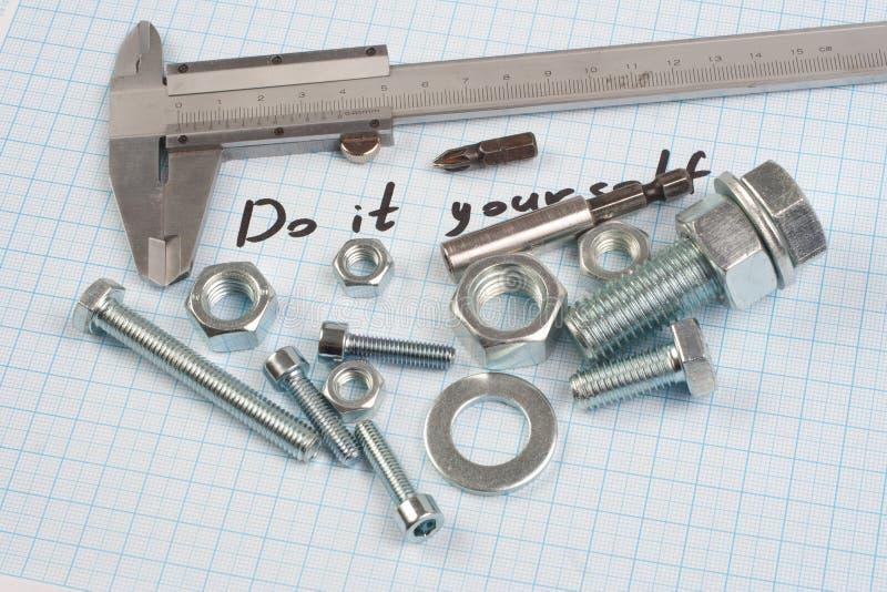 El ` lo hace usted mismo el ` - tornillo, nueces y calibrador en el papel cuadriculado foto de archivo libre de regalías