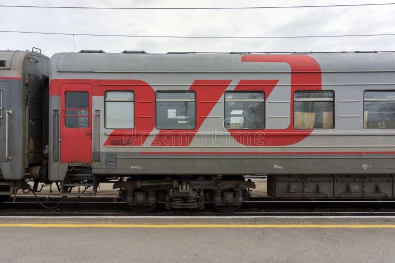 El logotipo RZD de una compañía de ferrocarriles rusa propiedad del gobierno grande se dibuja en un coche gris de un tren de pasa imágenes de archivo libres de regalías