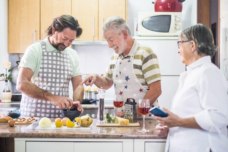 El lokking caucásico del cocinero de la gente del hombre de la familia tres junto cómo hacer en el teléfono móvil de la madre tod fotos de archivo libres de regalías