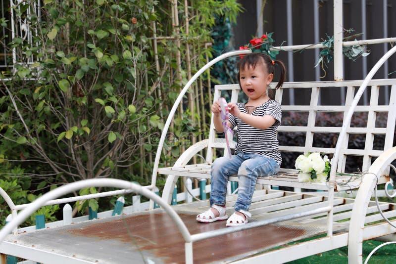 El lolipop adorable precioso travieso lindo feliz del juego de la niña y se sienta en un carro se divierte al aire libre en parqu foto de archivo