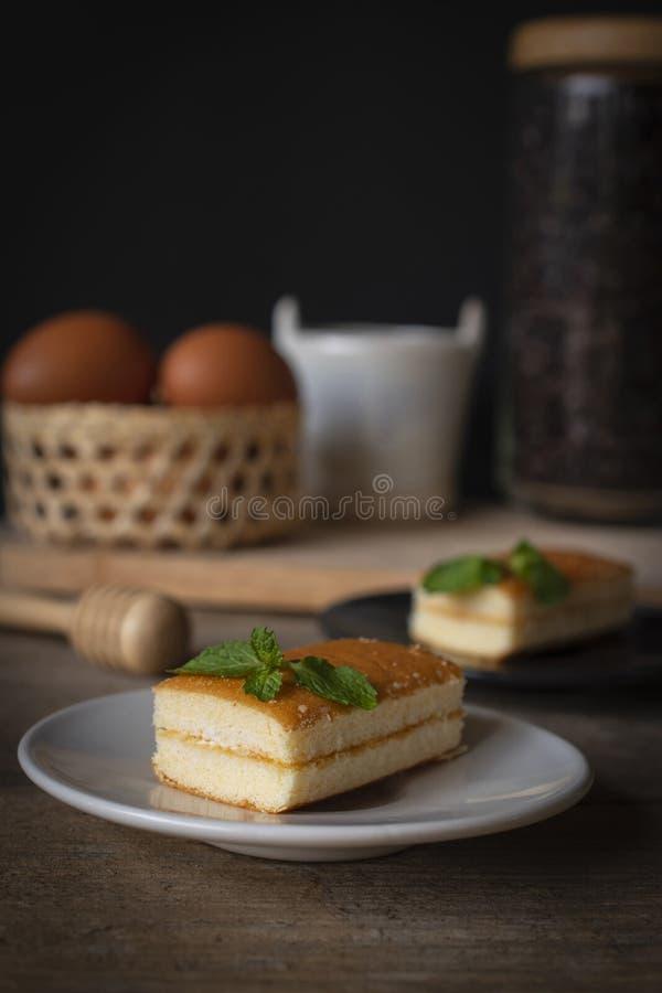El lugar con sabor a vainilla de la torta de la capa en la placa blanca en la tabla de madera allí es placa negra y grano de café imagenes de archivo