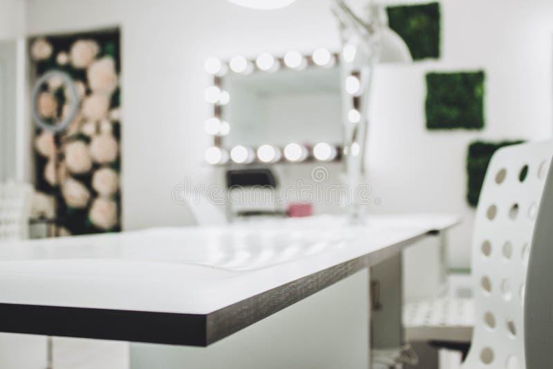 El lugar de trabajo del artista de maquillaje un espejo con las lámparas en una pared blanca y una butaca de madera foto de archivo libre de regalías