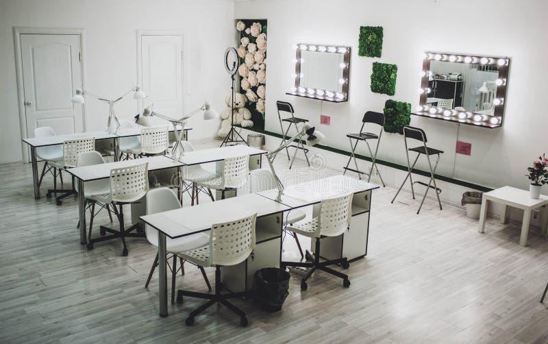 El lugar de trabajo del artista de maquillaje un espejo con las l?mparas en una pared blanca y una butaca de madera foto de archivo