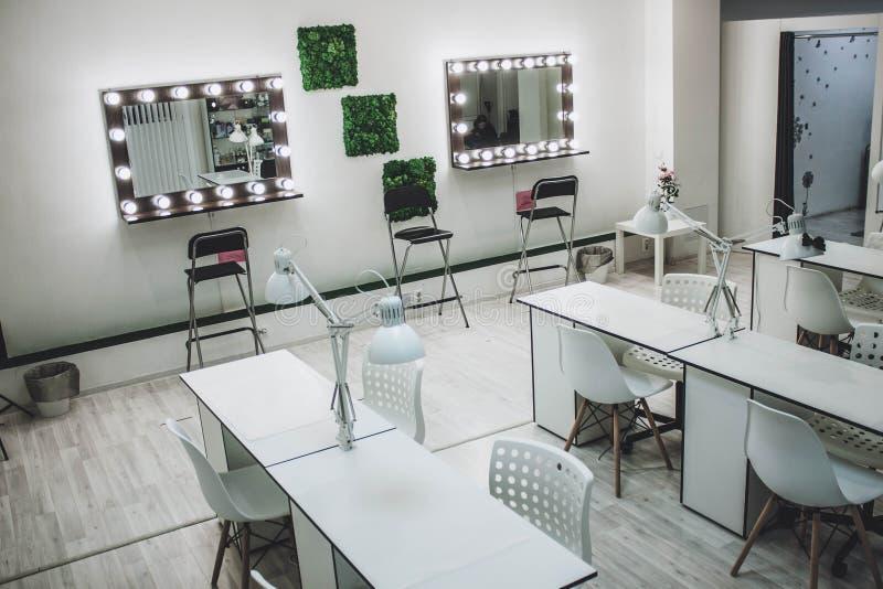 El lugar de trabajo del artista de maquillaje un espejo con las l?mparas en una pared blanca y una butaca de madera imagen de archivo