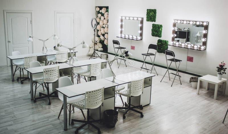 El lugar de trabajo del artista de maquillaje un espejo con las l?mparas en una pared blanca y una butaca de madera fotos de archivo