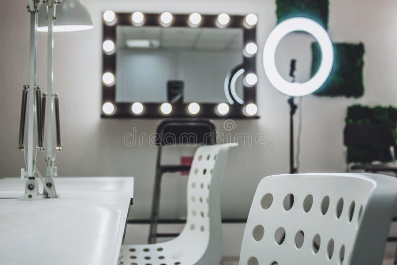 El lugar de trabajo del artista de maquillaje un espejo con las l?mparas en una pared blanca y una butaca de madera imagenes de archivo