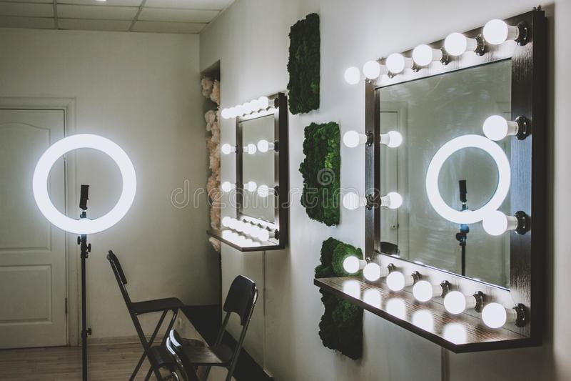 El lugar de trabajo del artista de maquillaje un espejo con las l?mparas en una pared blanca y una butaca de madera fotografía de archivo