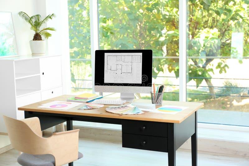 El lugar de trabajo del diseñador con las muestras de la paleta del ordenador y de la pintura en la tabla foto de archivo