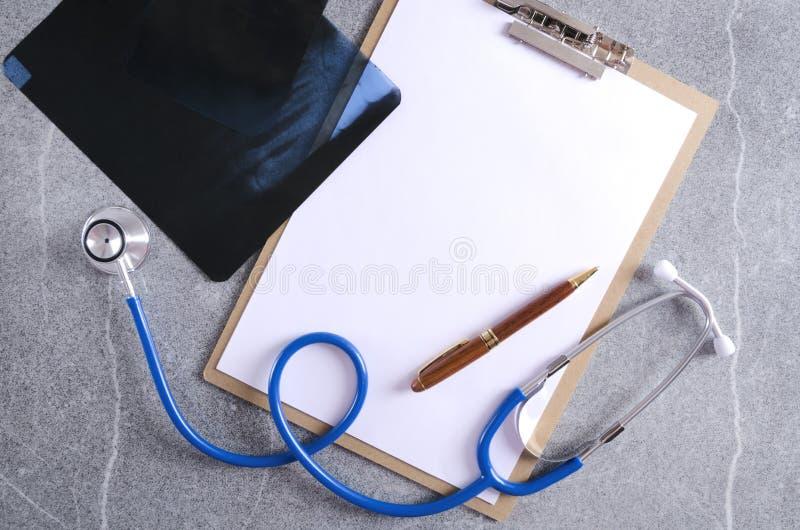 El lugar de trabajo del doctor profesional, estetoscopio, papel en blanco, pluma y radiografía fotos de archivo libres de regalías