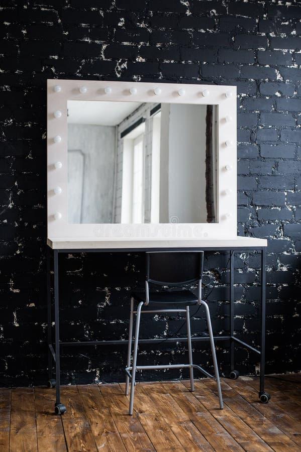 El lugar del maquillaje de la mujer con el espejo y los bulbos en el estudio de la foto loft la pared de ladrillo negra interior imagen de archivo libre de regalías