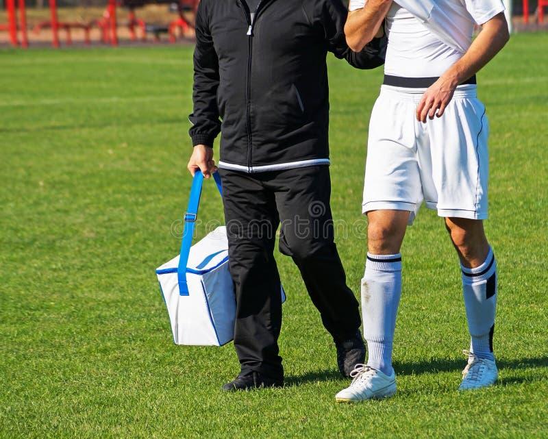 El médico ayuda al jugador de fútbol herido imagen de archivo libre de regalías