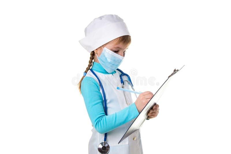 El médico o la enfermera de sexo femenino con el estetoscopio y la máscara escribe una nota en cuaderno contra el fondo blanco fotos de archivo libres de regalías