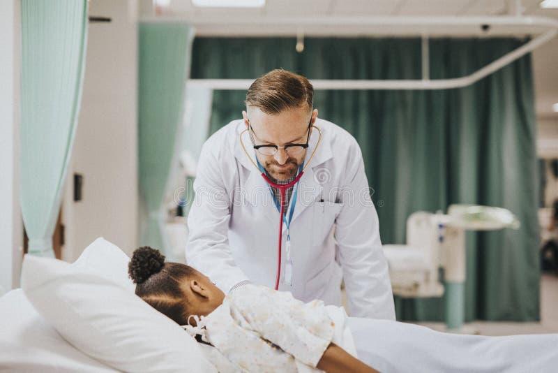 El médico que escuchaba el corazón batió de una niña foto de archivo