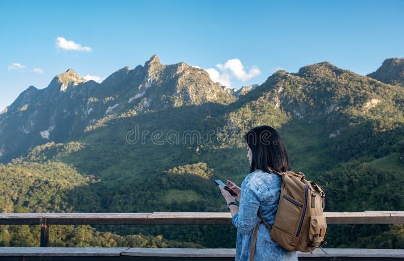 El móvil asiático del uso del viajero de la mujer en la opinión de la terraza de la montaña con la nube y el cielo azul en d fotos de archivo libres de regalías