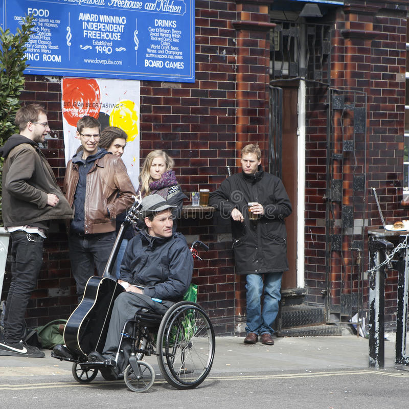 El músico con una guitarra en una silla de ruedas está sobre el pub, escuchando la música de los músicos de la calle foto de archivo libre de regalías