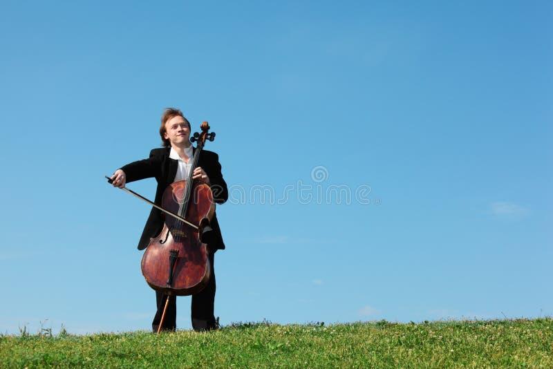 El músico juega el violoncello contra el cielo fotos de archivo libres de regalías