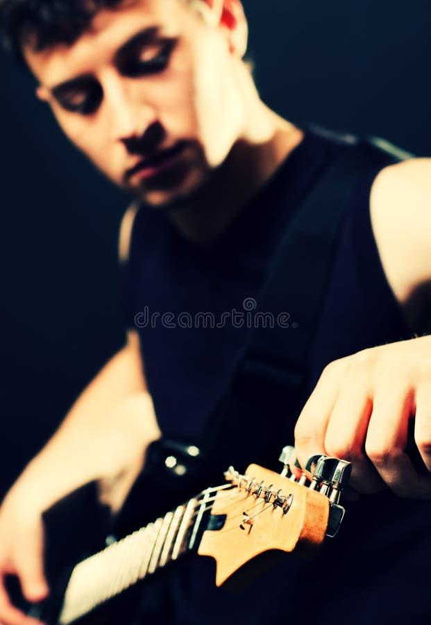 El músico templa para arriba la guitarra imagen de archivo