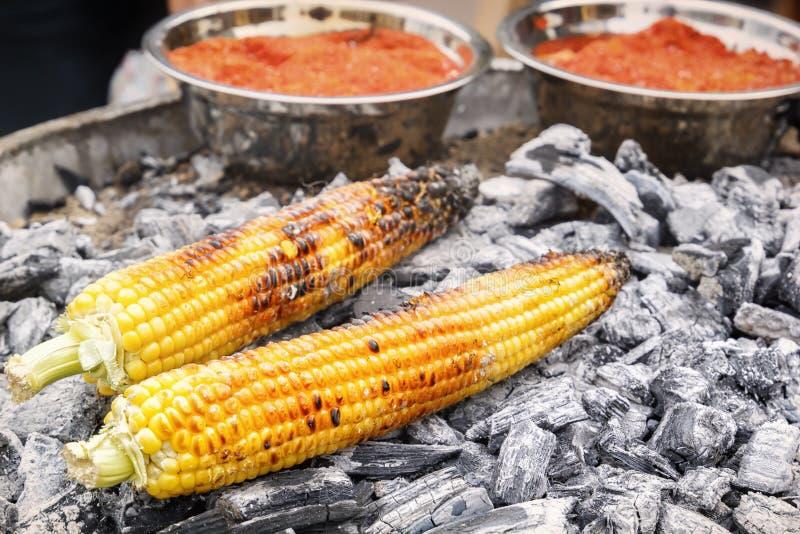 El maíz en estilo mexicano con la pimienta roja se cocina en los carbones calientes Alimentos de preparación rápida en la calle fotos de archivo libres de regalías