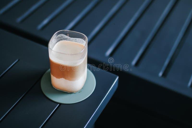 El macchiato de café helado sobre una mesa de madera con crema se vierte en ella mostrando la textura y el aspecto refrescante de fotos de archivo libres de regalías