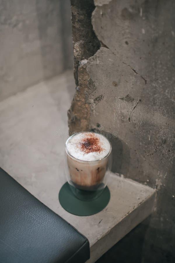 El macchiato de café helado sobre una mesa de madera con crema se vierte en ella mostrando la textura y el aspecto refrescante de fotografía de archivo