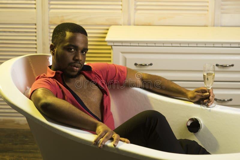El machista con la barba disfruta de vida con el vidrio de chamán en cuarto de baño de lujo Hombre en la cara relajada que se rel imagen de archivo libre de regalías