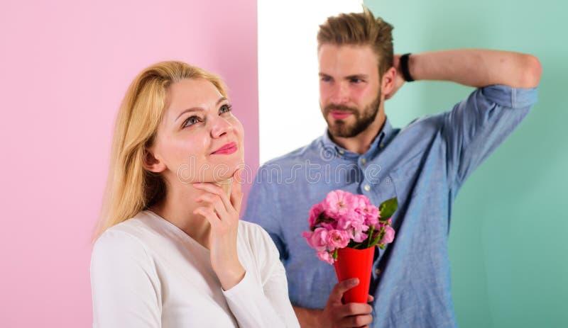 El machista le gusta sorprender a la mujer El ramo florece idea siempre agradable del regalo Fecha que espera de la muchacha para foto de archivo