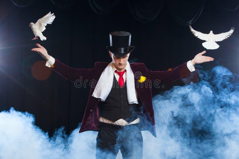 El mago con dos palomas blancas que vuelan en un fondo del negro cubierto en un humo misterioso hermoso fotografía de archivo