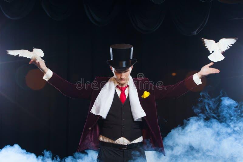 El mago con dos palomas blancas que vuelan en un fondo del negro cubierto en un humo misterioso hermoso fotos de archivo