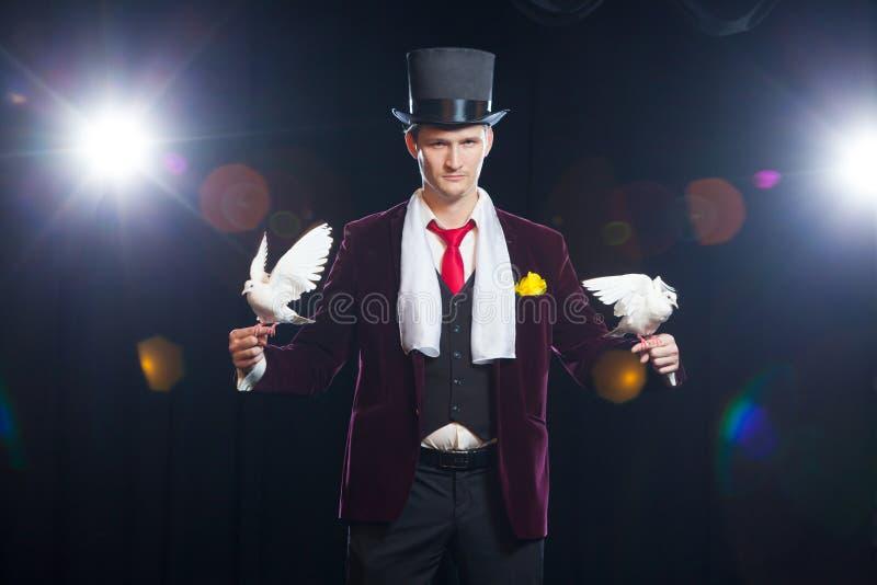 El mago con dos palomas blancas que vuelan En un fondo negro fotografía de archivo libre de regalías