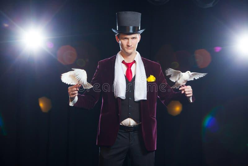El mago con dos palomas blancas que vuelan En un fondo negro fotos de archivo libres de regalías