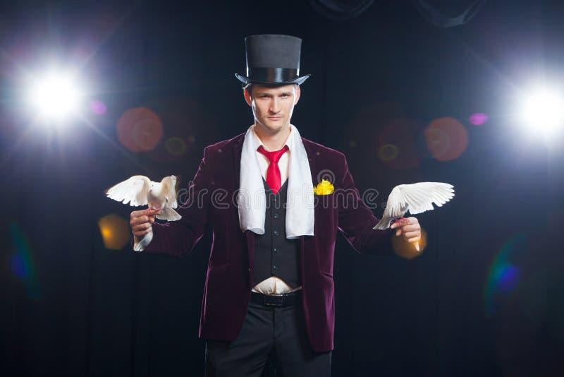 El mago con dos palomas blancas que vuelan En un fondo negro foto de archivo libre de regalías
