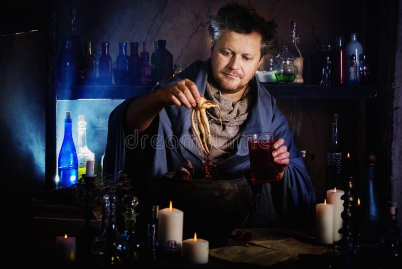 El mago elabora cerveza una poción imagen de archivo