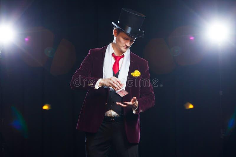 El mago, hombre del juglar, persona divertida, magia negra, demostración del hombre de la ilusión engaña con las tarjetas foto de archivo