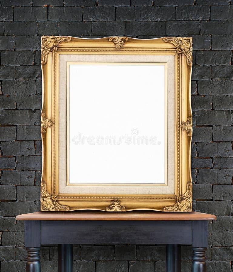 El magro de oro del marco de la foto del vintage en blanco en la pared de ladrillo negra encendido corteja imagen de archivo libre de regalías