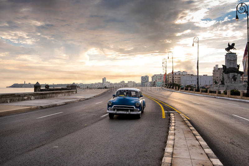 El Malecon famous sea fron promenade in Havana, Cuba. Havana, Cuba - September 22, 2015: Classic american car drive on Havana most popular sea fron promenade, El stock photography