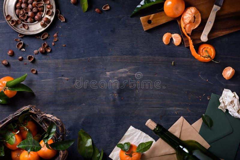 El mandarín da fruto con las avellanas y el vino en fondo de madera Marco sano del alimento biológico Visión superior, espacio de imagen de archivo libre de regalías