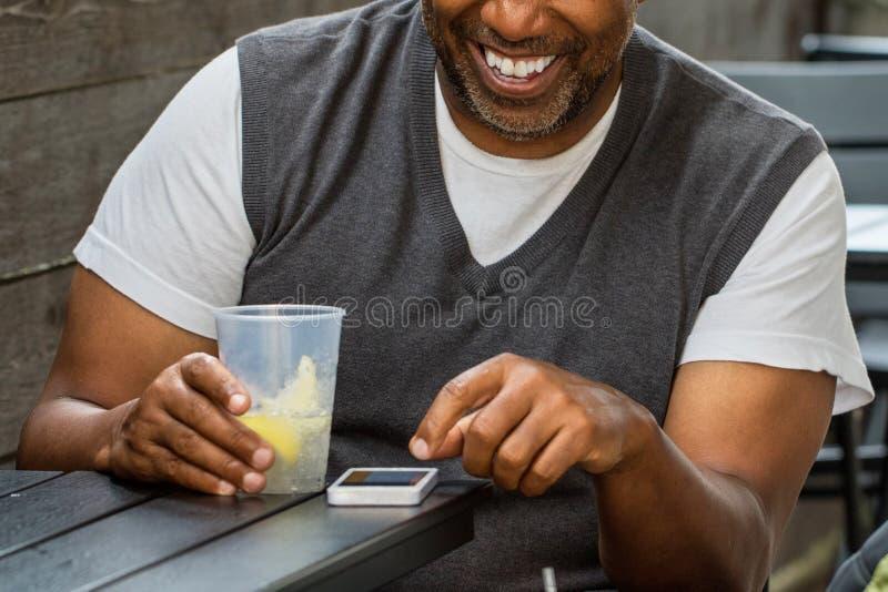 El mandar un SMS afroamericano del hombre fotos de archivo libres de regalías