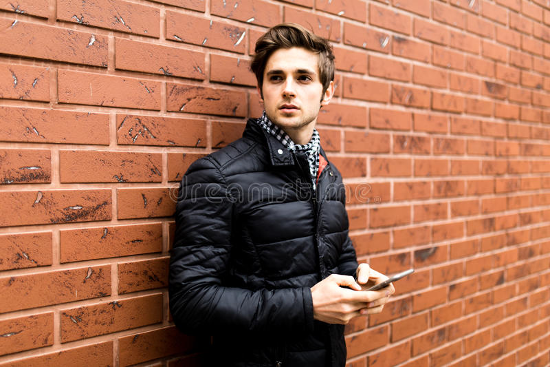 El mandar un SMS al hombre joven hermoso de la novia en la ropa de sport elegante que celebra el teléfono móvil mientras que se i imagenes de archivo